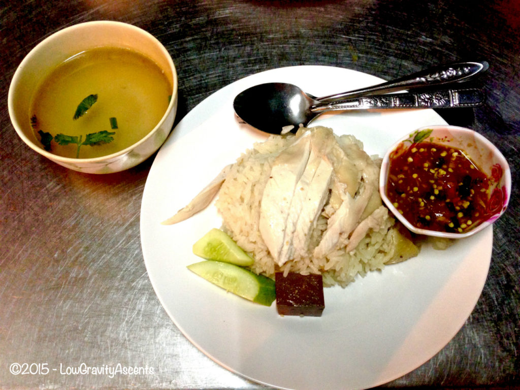 Boiled chicken over rice with broth and chili sauce